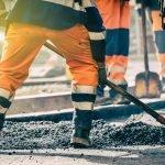 road workers shoveling gravel
