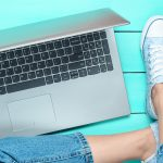 person wearing jeans and sneakers, sitting next to a laptop